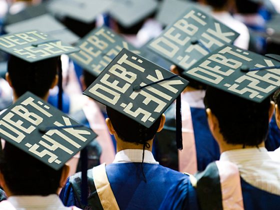 Student graduation caps with debt totals written on them.