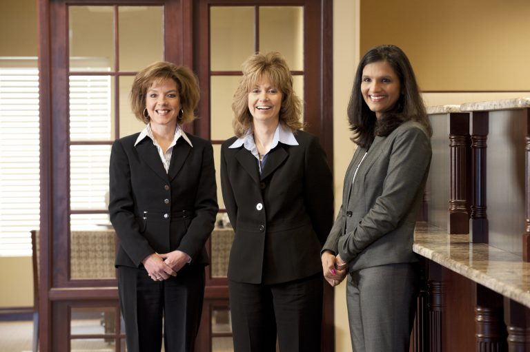 A group of female bankers smiling in the lobby.