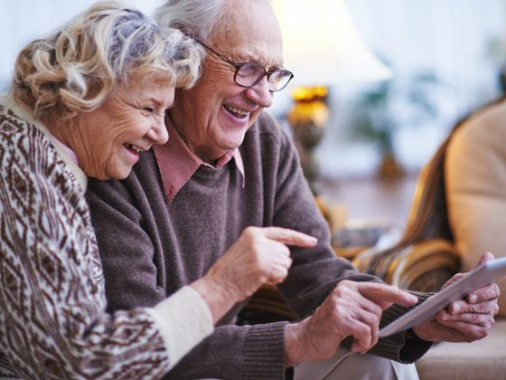 Seniors networking on tablet together.