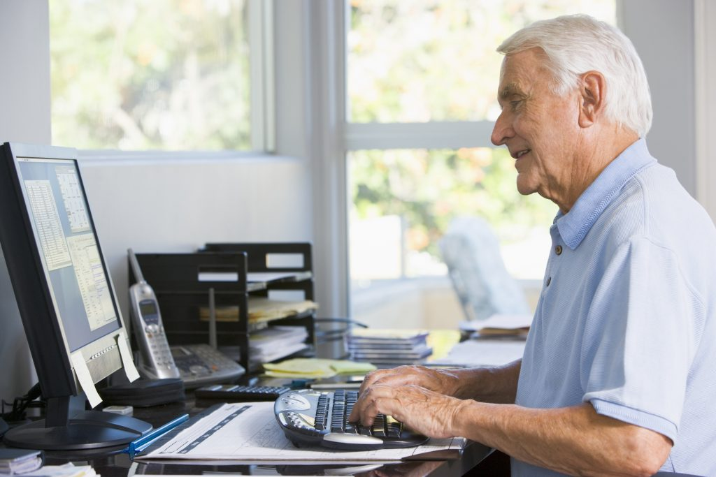 Older man in home office using computer smiling