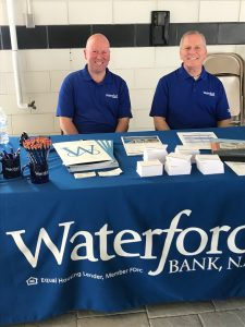bankers ready to greet customers at a trade show table.