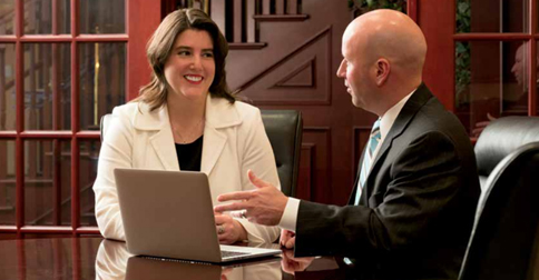 Treasury management representative shows customer how to use new computer technology.