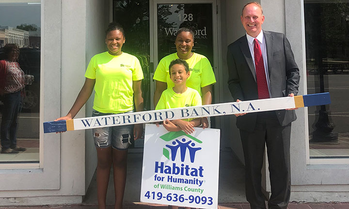 Community outreach - Male banker stands with habitat for humanity team holding a branded stud to be place in a new home.