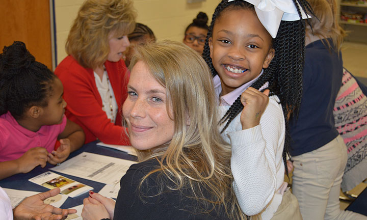 Community outreach - female bankers work with young girls to talk about saving money