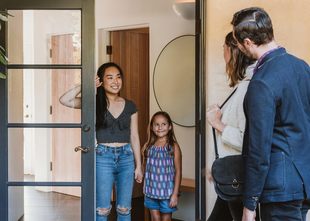 Parents leaving their smiling daughter with her happy female babysitter.