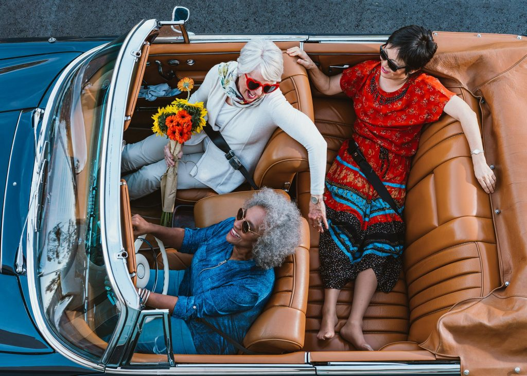 Three older ladies embarking on a road trip in their convertible.