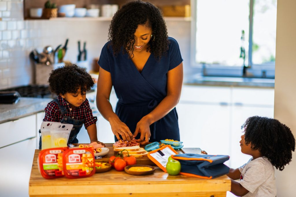 Mom teaching children to pack their lunches for school.