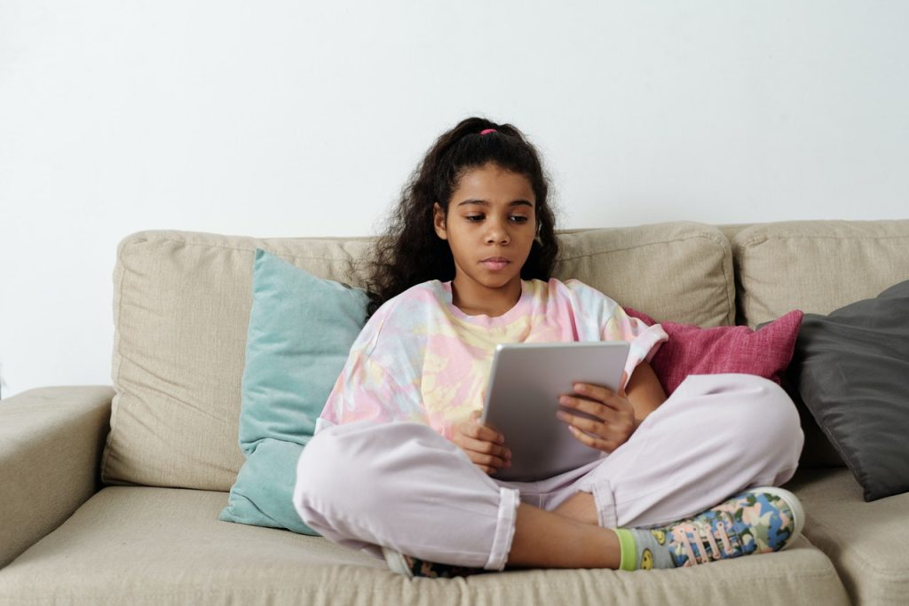 Young girl using tablet with online security.